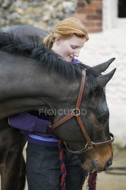 Mujer con caballo marrón oscuro - foto de stock