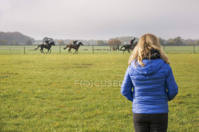 Woman standing and watching horse riders — Stock Photo