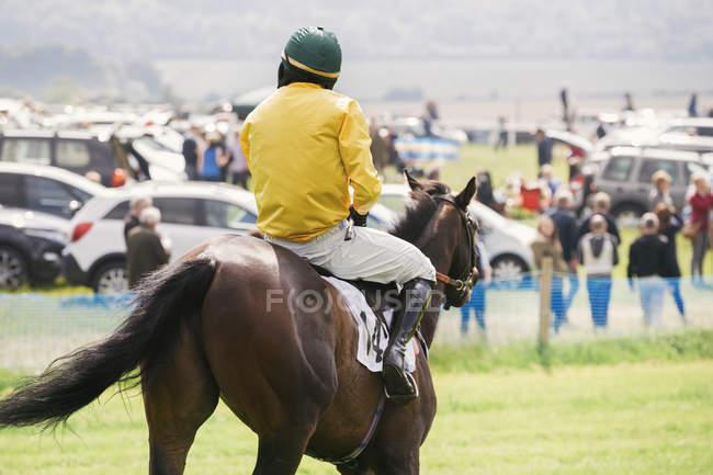 Jockey in riding race horse — Stock Photo