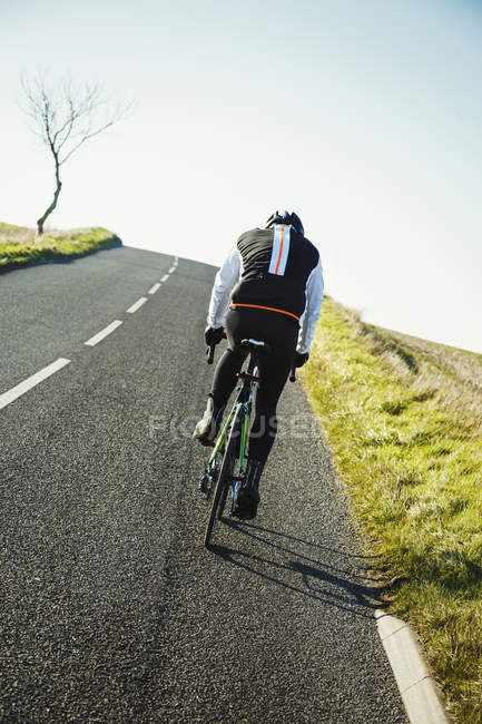 Cyclist pedaling along country road — Stock Photo