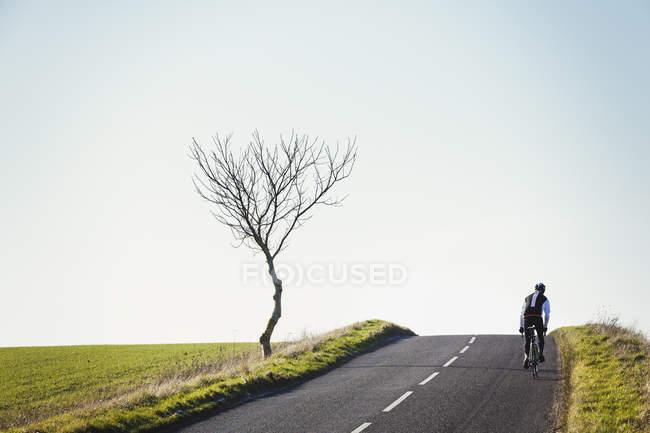 Велосипедист, педалей вдоль дороги страны — стоковое фото