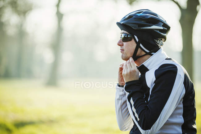 Cyclist adjusting chinstrap — Stock Photo