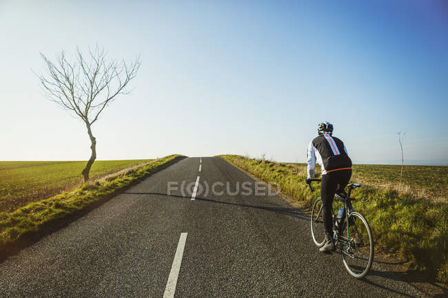 Cyclist riding along country road — Stock Photo