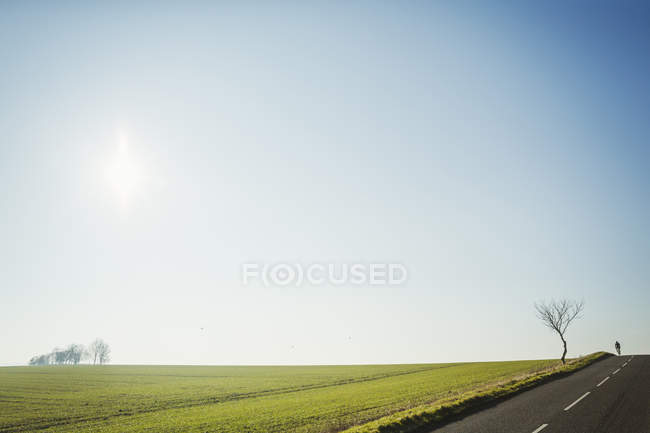 Man riding road bike on country road — Stock Photo