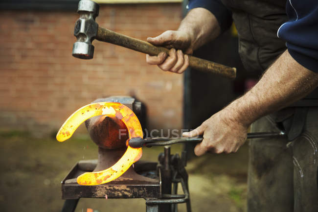 Farrier using tongs and hammer to hold horseshoe — Stock Photo