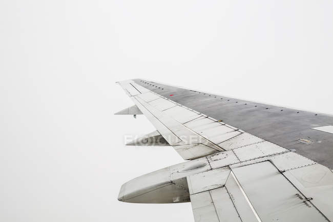 Крила літака під час польоту на сірий небо — стокове фото