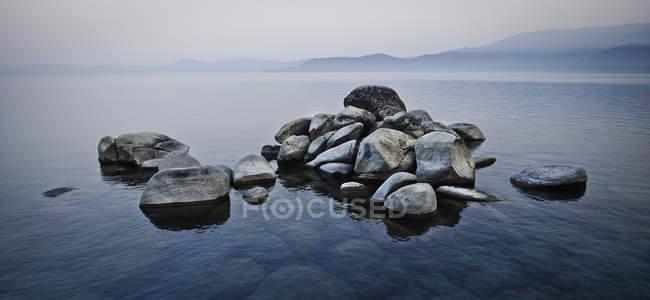 Груда камней, поднимающихся над водой — стоковое фото