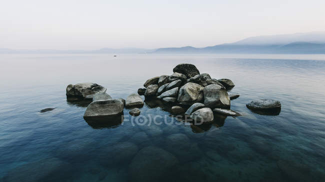 Pile of stones rising above water — Stock Photo