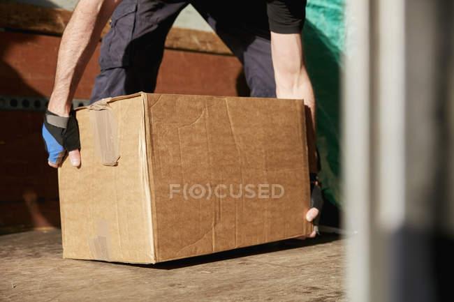 Homme soulevant la boîte en carton — Photo de stock