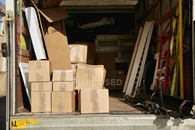 Déménagements van avec boîtes empilées et éléments — Photo de stock