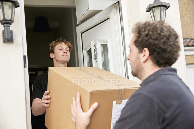 Dos hombres levantando y cargando caja - foto de stock