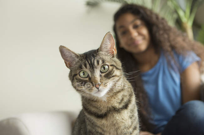 Girl sitting on sofa with pet cat — Stock Photo