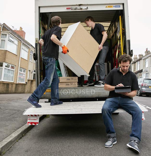 Dois homens levantando móveis — Fotografia de Stock