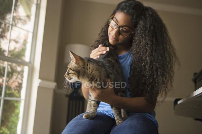 Muchacha con gato en el regazo - foto de stock