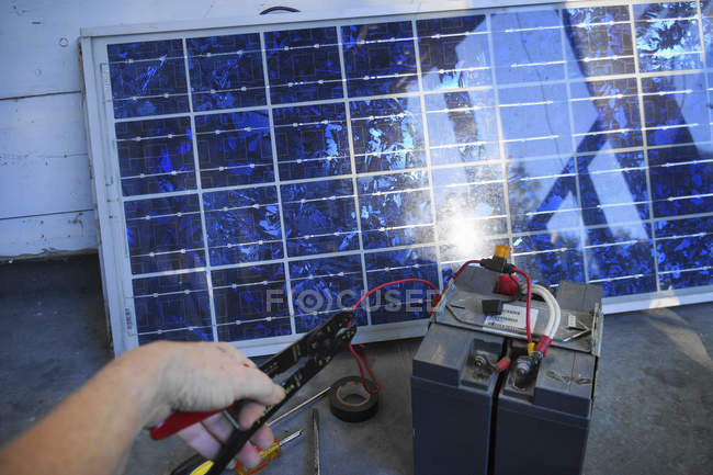 Hombre usando alicates y herramientas para colocar la batería - foto de stock