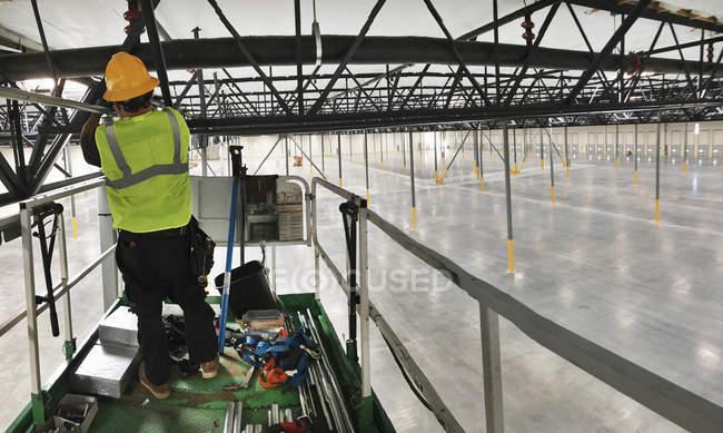 Man in hard hat working on metal gantry — Stock Photo