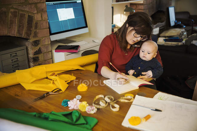 Woman seated with baby on lap writing in notebook — Stock Photo