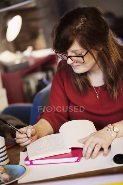 Woman seated at table and making notes — Stock Photo