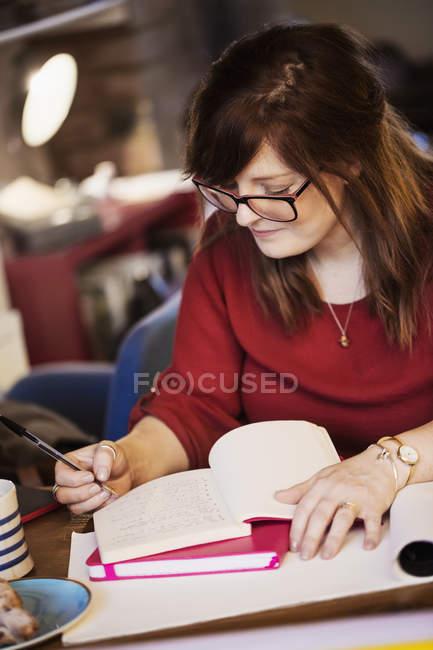 Жінка, сидячи на таблиці та рішень нотатки — стокове фото