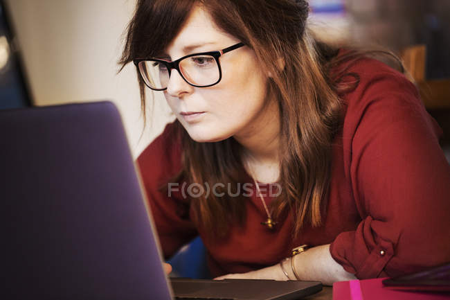 Woman seated using laptop — Stock Photo