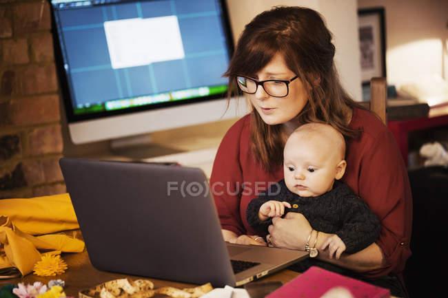 Женщина сидит с ребенком на коленях — стоковое фото