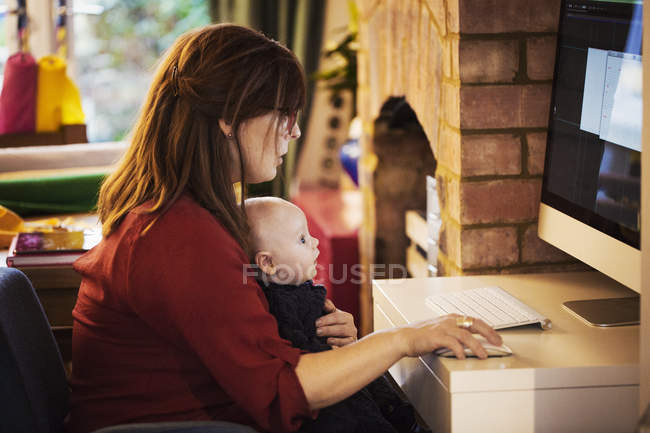 Woman seated with baby on lap using computer — Stock Photo