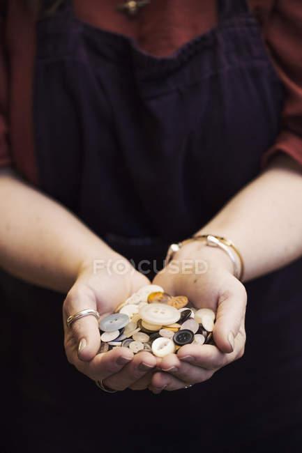Mulher segurando as mãos cheias de botões — Fotografia de Stock