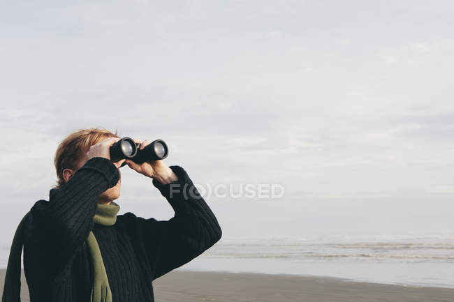 Man standing on beach and looking through binoculars — Stock Photo