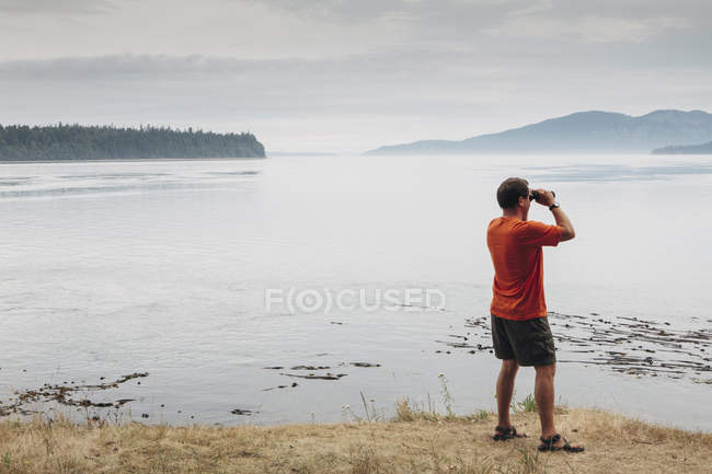 Man standing on beach and looking through binoculars — Stock Photo