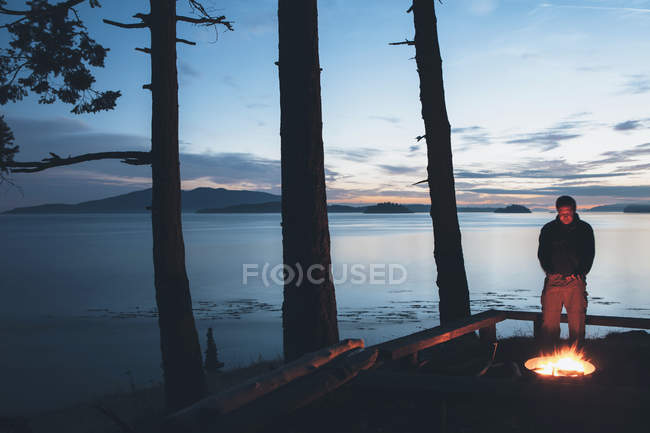 Man standing by campfire at dusk — Stock Photo