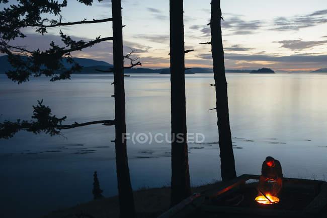 Uomo seduto al falò al crepuscolo — Foto stock