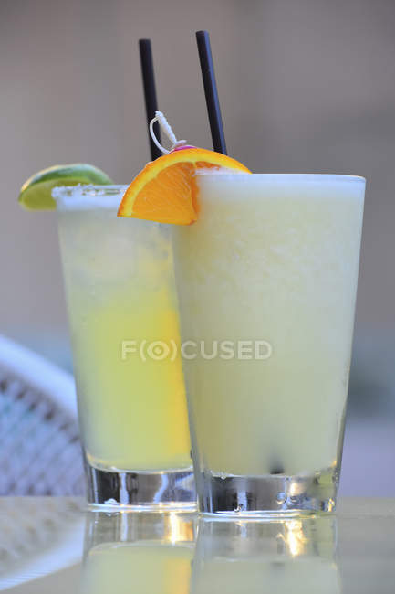 Cocktails with straws and citrus garnishes — Stock Photo