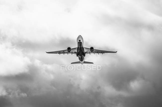 Avión en vuelo en cielo nublado - foto de stock