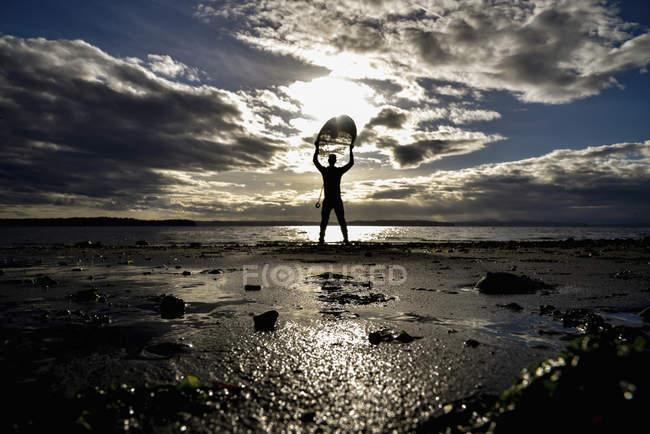 Man standing on beach holding surfboard — Stock Photo
