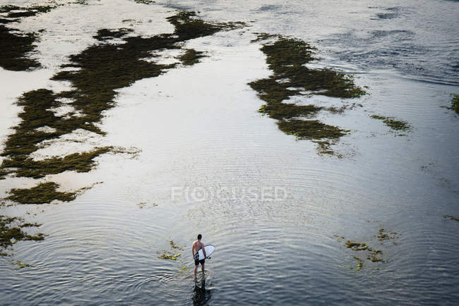Mann, der im flachen Meerwasser — Stockfoto