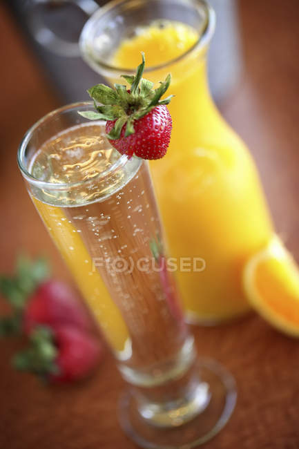 Carafe of orange juice and glass of champagne — Stock Photo