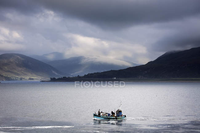 People in fishing boat on large body of water — Stock Photo