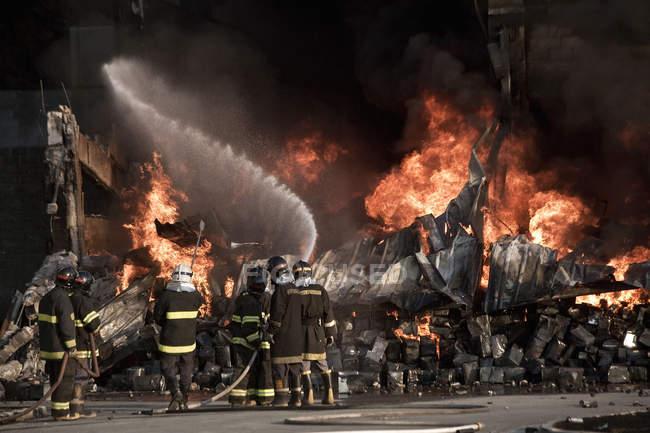 Kämpfer Aufsprühen von Wasser auf Feuer — Stockfoto