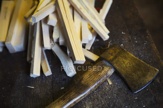 Wooden pegs and hand axe — Stock Photo