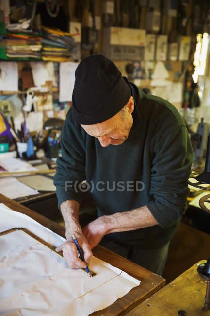 Мужчина измеряет кусок ткани для паруса . — стоковое фото