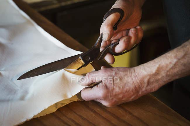 Mancutting piece of sailcloth — Stock Photo