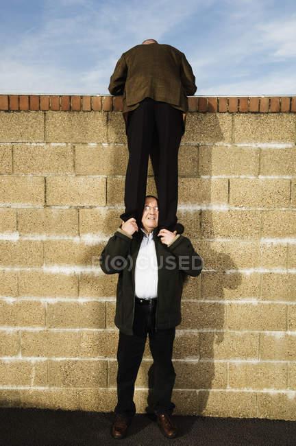 Uomo che si arrampica sul muro di mattoni giallo — Foto stock