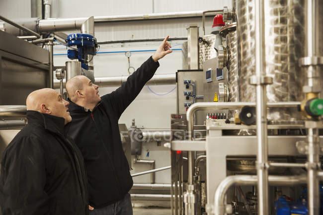 Two men checking a metal tank — Stock Photo