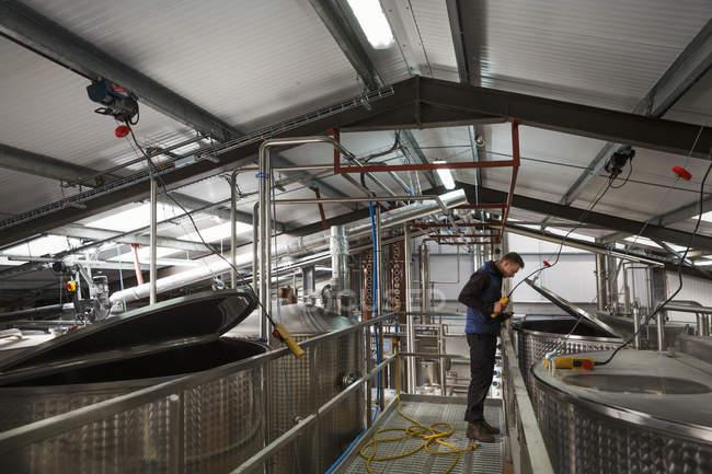 Man checking large metal tanks — Stock Photo