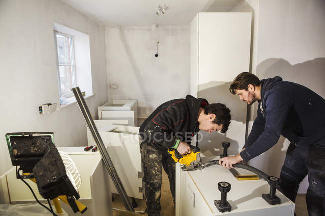 Builders, cutting plasterboard — Stock Photo