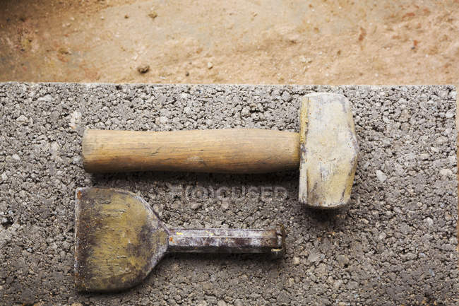 Hammer and chisel on a concrete slab. — Stock Photo