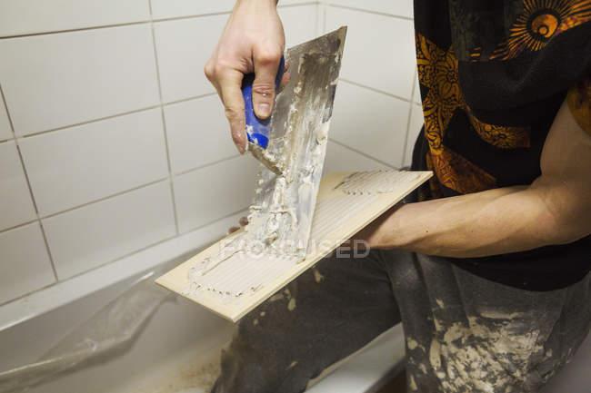 Особі поширення клею на плитку. — стокове фото
