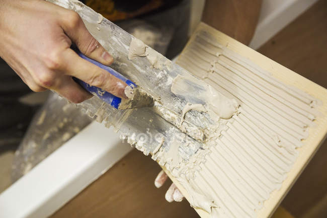 Tiler spreading adhesive on a tile. — Stock Photo