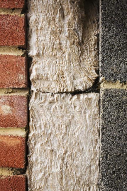 Insulation between a brick and cinder block wall. — Stock Photo