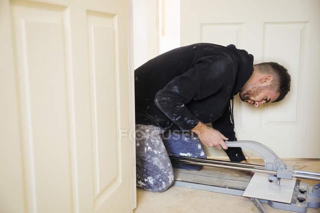 Builder, tiler kneeling on the floor — Stock Photo